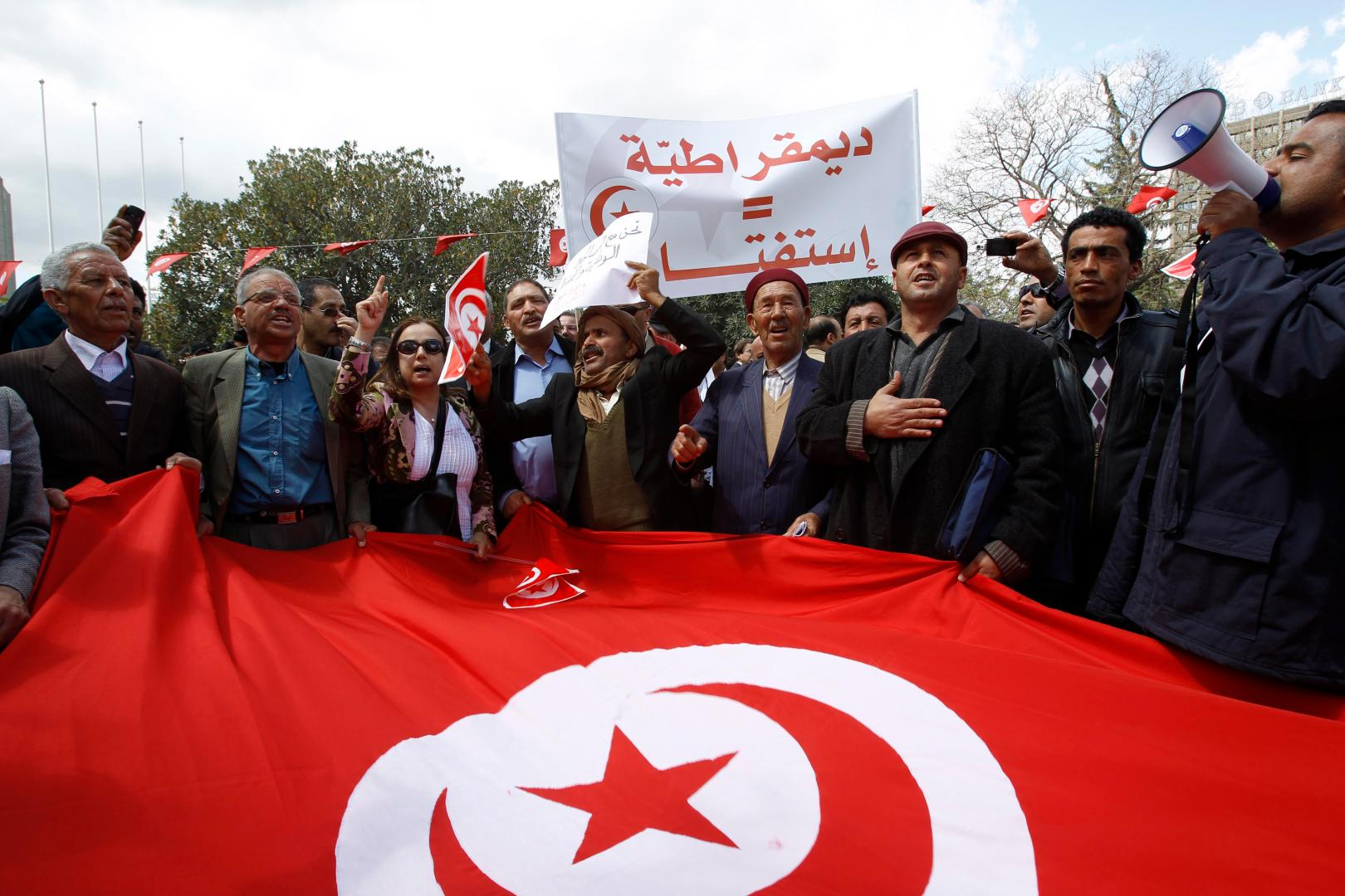 Supporters of Tunisia's ousted president Zine Al-Abidine Ben Ali's Constitutional Democratic Rally (RCD) party hold a protest against what they said was their their marginalization by society and to demand their right to participate in the country's political life, in Tunis April 16, 2011. A Tunisian judge ruled in March that the RCD was to be disbanded and its funds seized. The party's former senior members were also banned from taking part in upcoming July elections. The sign reads,