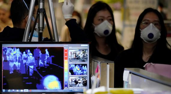 Passengers wearing masks to prevent contracting coronavirus walk past a thermal camera upon their arrival at Incheon International Airport in Incheon, South Korea.