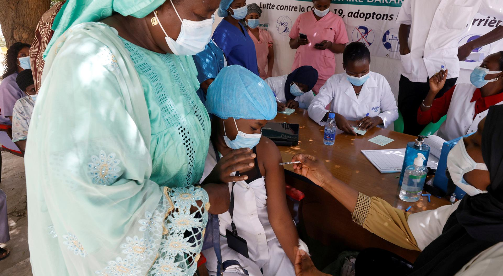 A health worker reacts as she receives a dose of coronavirus disease (COVID-19) vaccine in Dakar, Senegal