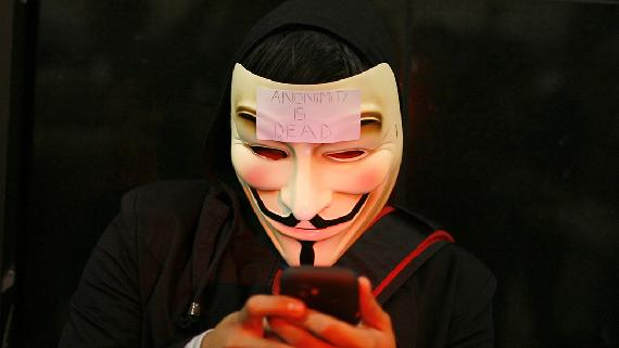 A masked protester is using his mobile phone.