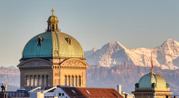 Federal Palace in Bern. Central and western domes in evening light with the peaks of Eiger and Mönch in the background
