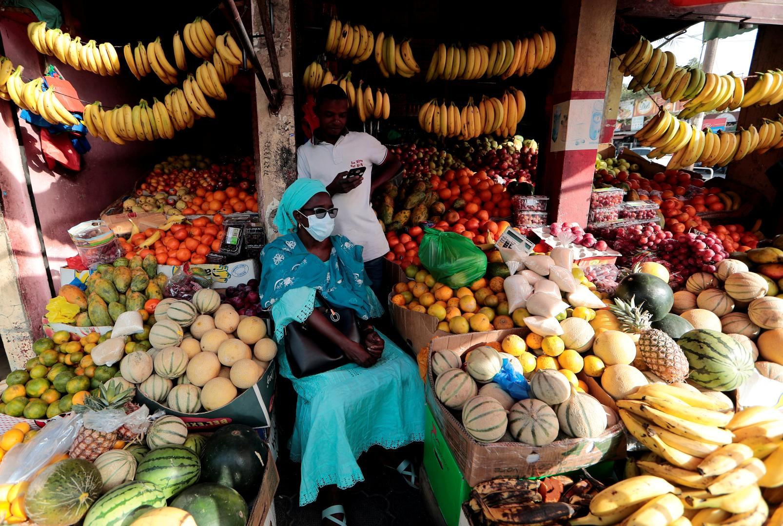 Senegal, A woman wears a protective face mask as she waits to get her change after buying fruits
