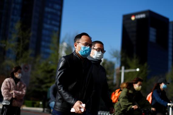 People wear masks as they head to work during morning rush hour amid the outbreak of coronavirus disease..Asia