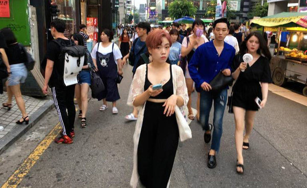 Younger South Koreans stroll through the bustling Hongdae district of Seoul on July 21, 2017. Millennials in South Korea were once maligned as politically detached, but they turned out in force this year to oust the nation's previous president and elect a new one. (Stuart Leavenworth/McClatchy/TNS)