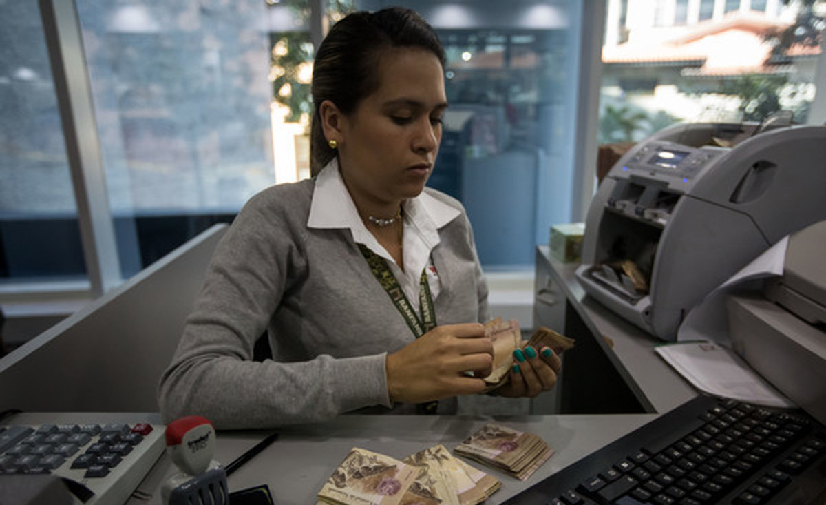 Bank workers count 100 bolivar notes in Caracas, Venezuela, 15 December 2016. The Central Bank of Venezuela set the amount of bolivares in cash that a person can carry when crossing the border, as the Government assures alleged attacks on the national currency. EFE/Miguel Gutierrez |