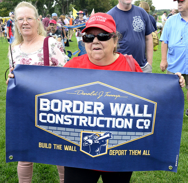 "woman wearing a ""make America great again"" hat, holds a poster that says ""Trump's Border Wall Construction company, build the wall deport them all"""