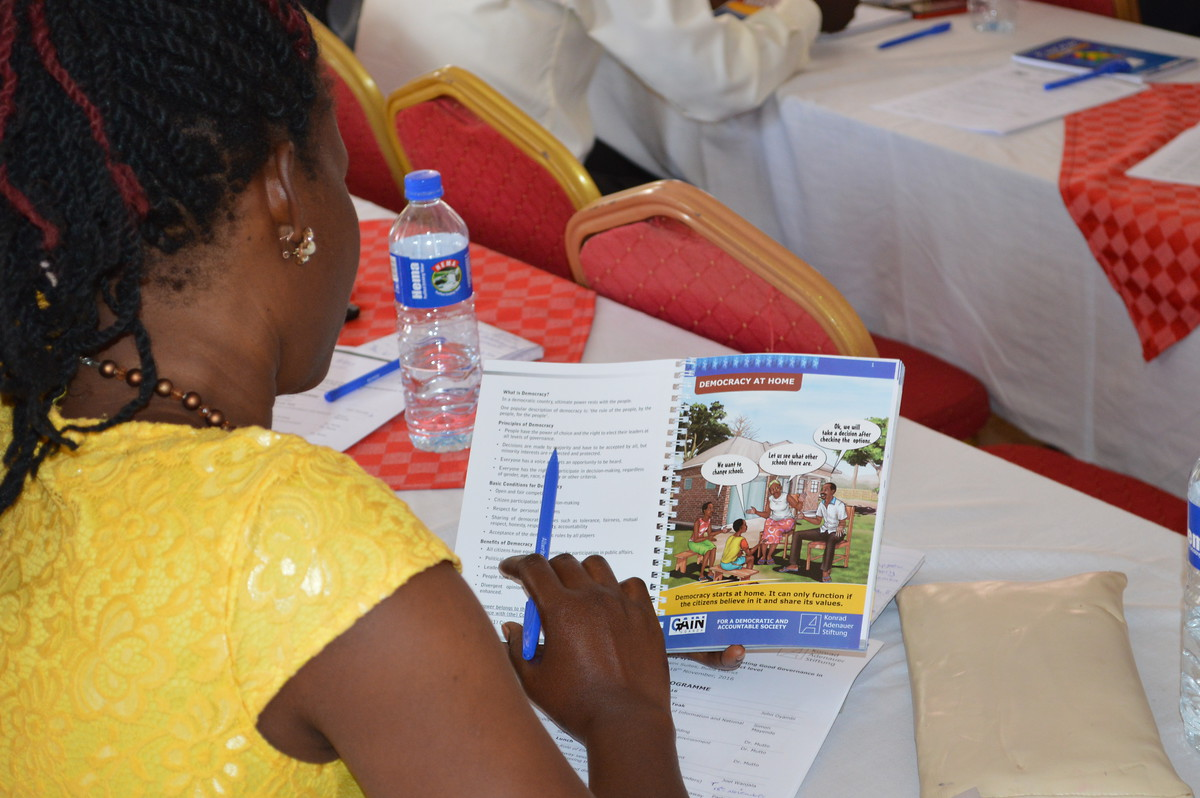 Participants reading through KAS' new civic education material