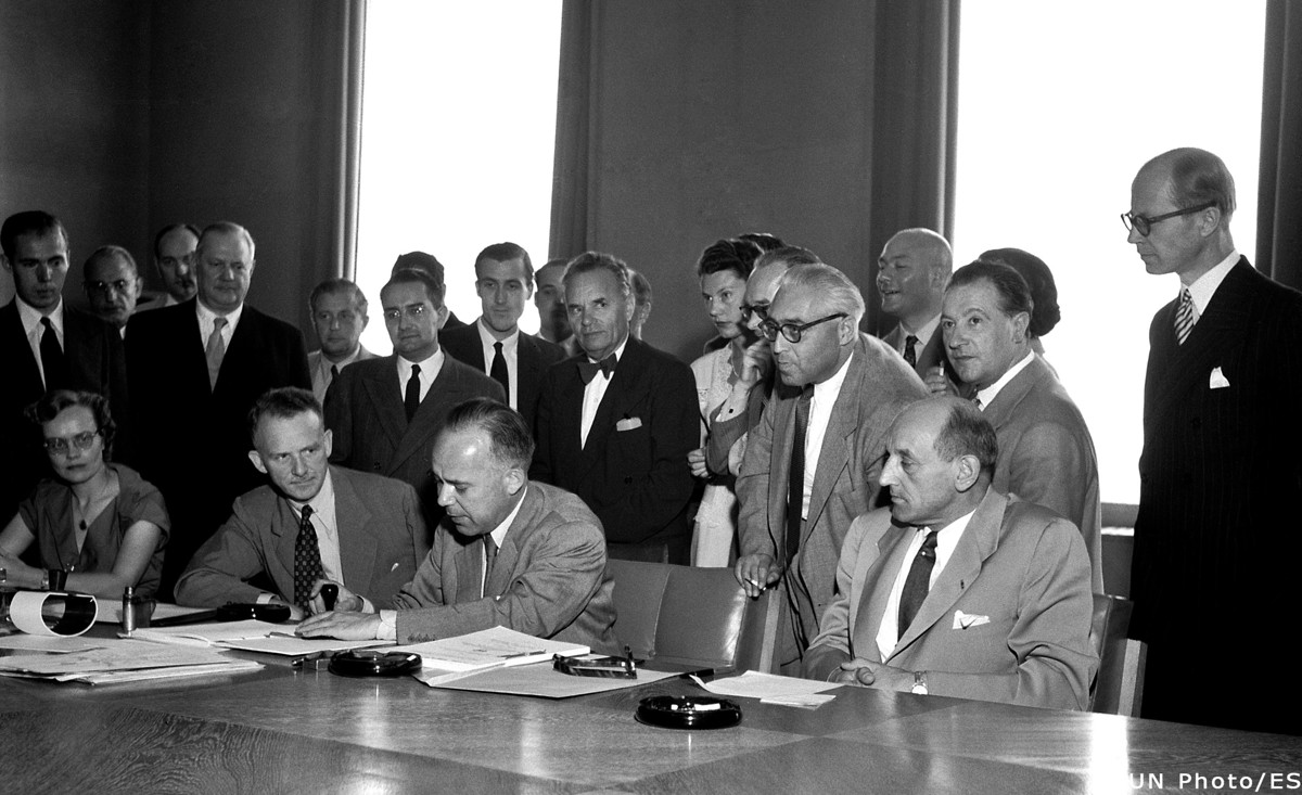 Signature of the 1951 Refugee Convention in Geneva, Switzerland / the three seated men (l-r): Mr. John Humphrey, Director of the Human Rights Division; Mr. Knud Larsen (Denmark) President of the Conference; Dr. G.V. van Heuven Goedhart, High Commissioner for Refugees
